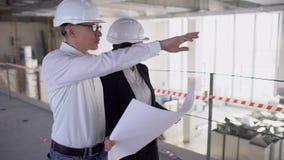 El ingeniero o el arquitecto de sexo femenino confiado que discute la construcción publica con el colega masculino A cámara lenta almacen de video