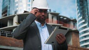 El ingeniero o el arquitecto adulto utiliza una tableta en funcionamiento Escribe un mensaje o comprueba un dibujo Contra fondo e metrajes