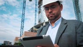 El ingeniero o el arquitecto adulto utiliza una tableta en funcionamiento Escribe un mensaje o comprueba un dibujo Contra fondo e almacen de metraje de vídeo