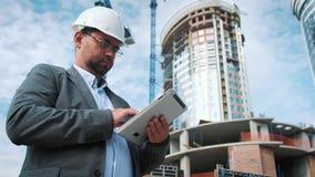 El ingeniero o el arquitecto adulto utiliza una tableta en funcionamiento Escribe un mensaje o comprueba un dibujo Contra fondo e almacen de video
