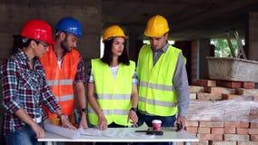 El ingeniero o el arquitecto que discute la construcción publica con los colegas almacen de video