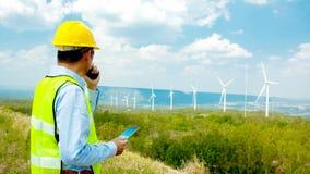 El ingeniero o tecnician masculino en la estación de la turbina de viento del trabajo, enrolla ene fotografía de archivo