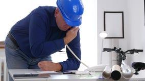 El ingeniero ocupado en sitio de la oficina intenta hacer una llamada de teléfono usando una línea horizonte técnica metrajes