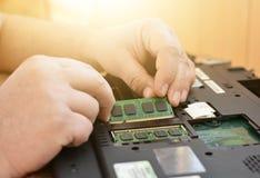 El ingeniero restaura la PC del ordenador portátil Instalación del hardware del disco duro, RAM Taller de reparaciones electrónic Fotografía de archivo