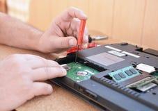 El ingeniero restaura la PC del ordenador portátil Instalación del hardware del disco duro, RAM Taller de reparaciones electrónic fotos de archivo