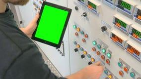El ingeniero se coloca en el frente del panel de control y de sostener una tableta con la pantalla verde almacen de video