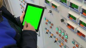 El ingeniero se coloca en el frente del panel de control y de sostener una tableta con la pantalla verde metrajes