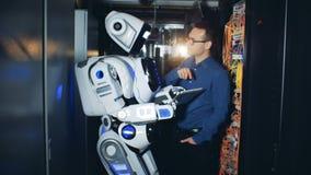 El ingeniero trabaja con un robot en un cuarto del servidor, cierre para arriba