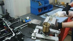 El ingeniero vierte el aceite para lo substituye en la bifurcación de la dirección almacen de video