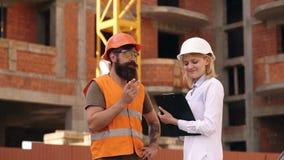 El ingeniero y el constructor de la mujer comunican en el emplazamiento de la obra Concepto de la comunicación del equipo de la c almacen de video