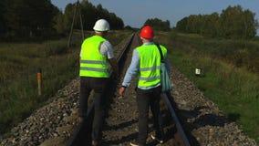 El ingeniero y el trabajador en pista ferroviaria discuten trabajos almacen de metraje de vídeo