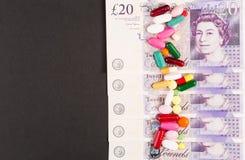 El inglés golpea billetes de banco con las píldoras o las cápsulas derramadas imagen de archivo libre de regalías