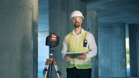 El inspector de construcción de sexo masculino es dispositivo que examina de la tierra cercana derecha y trabajo en su tableta metrajes