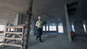 El inspector de construcción de sexo masculino está caminando rápidamente a través del emplazamiento de la obra metrajes