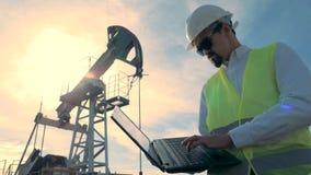 El inspector de la gasolina está trabajando con un ordenador cerca de una aceite-torre de perforación de bombeo, bomba de aceite  almacen de metraje de vídeo