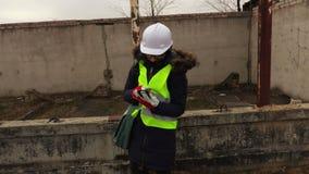 El inspector de la mujer toma imágenes en smartphone en la construcción de un edificio metrajes