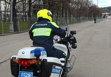 El inspector de la patrulla de la policía del camino en la motocicleta del servicio controla el camino Imágenes de archivo libres de regalías