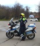 El inspector de la patrulla de la policía del camino en la motocicleta del servicio controla el camino Imagen de archivo libre de regalías