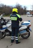 El inspector de la patrulla de la policía del camino en la motocicleta del servicio controla el camino Fotografía de archivo
