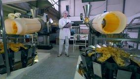 El inspector de sexo femenino está controlando la distribución mecánica de patatas a la inglesa almacen de metraje de vídeo