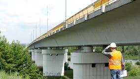 El inspector de sexo masculino del inspector examina el estado del puente, controles, visitante almacen de video