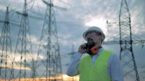 El inspector de sexo masculino está hablando en un teléfono delante de torres de la electricidad metrajes