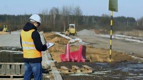 El inspector del ingeniero mira y escribe datos durante una fase de construcción de carreteras antes de poner del material del pa almacen de metraje de vídeo