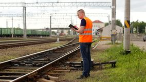 El inspector examina controles el mecanismo del interruptor automático en el ferrocarril, mecanismo ferroviario del interruptor e almacen de metraje de vídeo