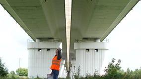 El inspector jefe examina el puente del coche sobre el río, el inspector y el puente almacen de metraje de vídeo