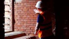 El inspector joven comprueba la densidad de paredes de ladrillo, preparación para la reconstrucción, arquitecto almacen de video