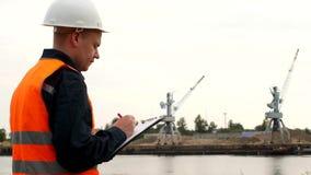 El inspector registra los problemas identificados en la operación de las grúas del puerto en el puerto almacen de video
