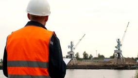 El inspector registra los problemas identificados en la operación de las grúas del puerto en el puerto almacen de metraje de vídeo