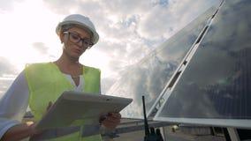 El inspector solar de sexo femenino está trabajando en su ordenador mientras que se coloca en los tejados almacen de metraje de vídeo