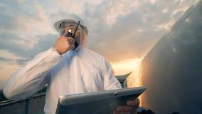 El inspector solar está hablando en un transmisor mientras que se coloca en un tejado almacen de video
