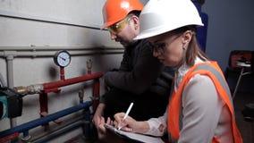 El inspector y el trabajador comprueban el sistema de calefacción Ingeniero hermoso de la mujer almacen de video