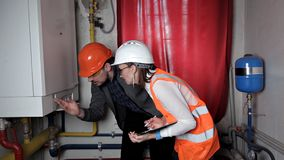 El inspector y el trabajador comprueban el sistema de calefacción Ingeniero hermoso de la mujer metrajes