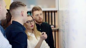 El inspirarse en la oficina Los colegas discuten el problema y hacen notas en un tablero blanco metrajes