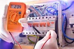 El instalador eléctrico con los elementos protectores que hacen medidas eléctricas se cierra para arriba fotografía de archivo