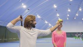 El instructor aplaude al jugador de tenis en hombro y va lejos después de su golpe fracasado almacen de video
