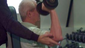 El instructor ayuda al cliente mayor durante el entrenamiento metrajes