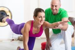 El instructor ayuda al principiante a hacer actitud de la yoga imagen de archivo libre de regalías