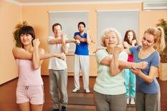 El instructor ayuda a la mujer mayor con ejercicio de la yoga imagen de archivo libre de regalías