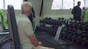 El instructor da pesas de gimnasia al cliente mayor metrajes