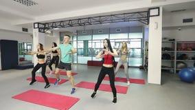 El instructor de la aptitud está trabajando con las mujeres jovenes en gimnasio metrajes