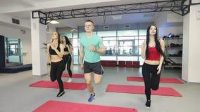 El instructor de la aptitud está trabajando con las mujeres jovenes en gimnasio almacen de video