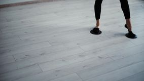 El instructor de la aptitud de la mujer mueve los pies que resbalan la estera en piso en gimnasio en la cámara lenta metrajes