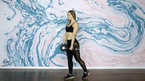 El instructor de la aptitud que hace posiciones en cuclillas con pesas de gimnasia mujer atlética y hermosa almacen de video