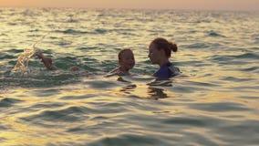 El instructor de la natación de la mujer enseña a la natación del niño pequeño en un mar durante un sundet metrajes