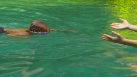 El instructor de la natación de la mujer joven enseña un niño pequeño a cómo nadar en una piscina almacen de metraje de vídeo