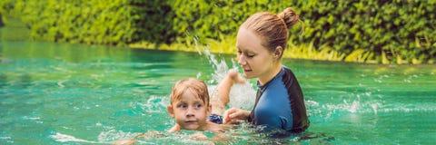El instructor de la natación de la mujer para los niños está enseñando a un muchacho feliz a nadar en la BANDERA de la piscina, f foto de archivo